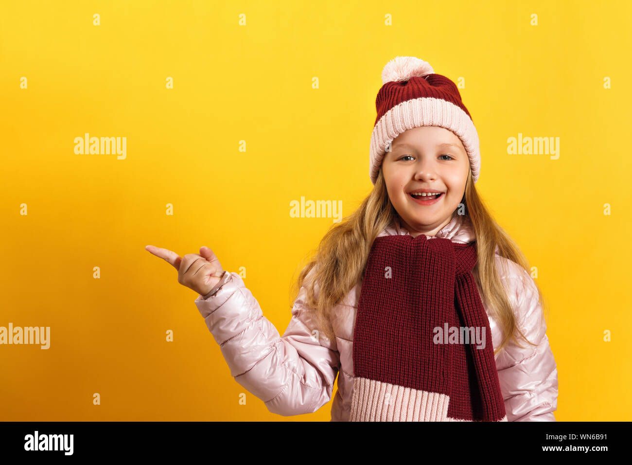 Little girl in a jacket, scarf and hat on a yellow background. The child shows the index finger to the side. - Stock Photo