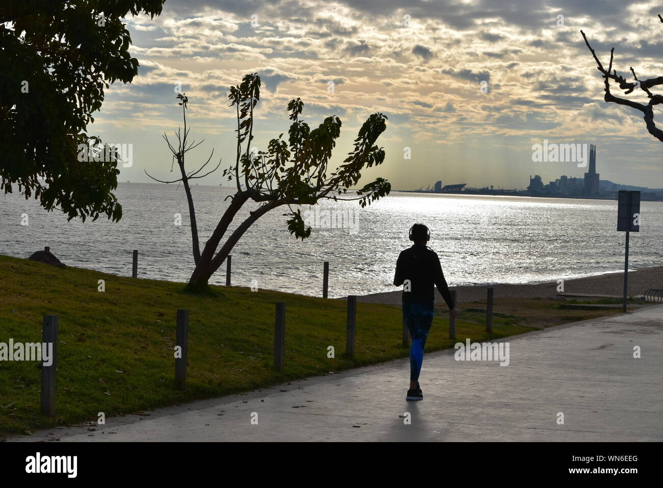 Rear View Of Woman Walking On Promenade Against Sky During Sunset Stock Photo