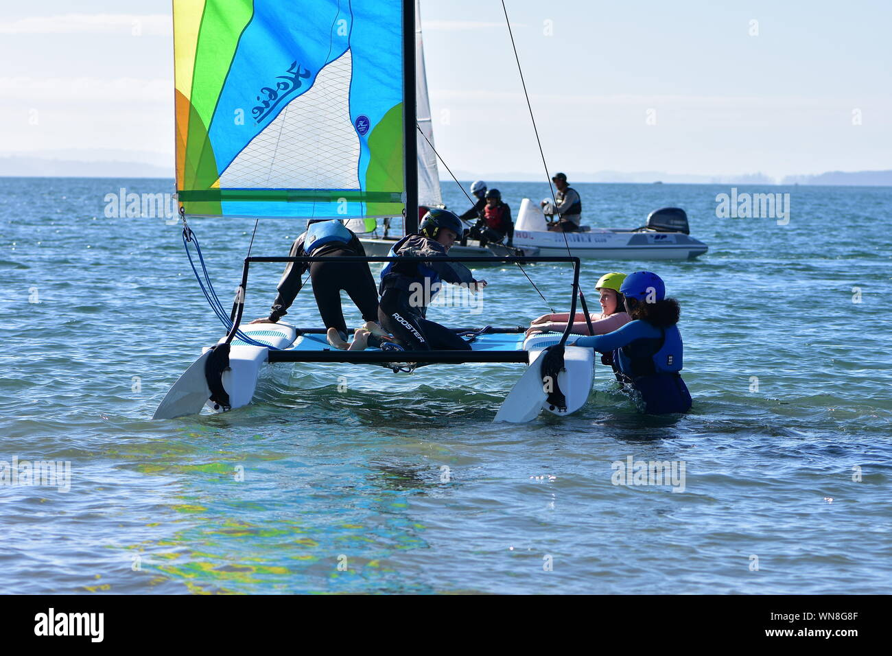 Crew of young girls boarding their racing sailing catamaran for training in shallow bay. Stock Photo
