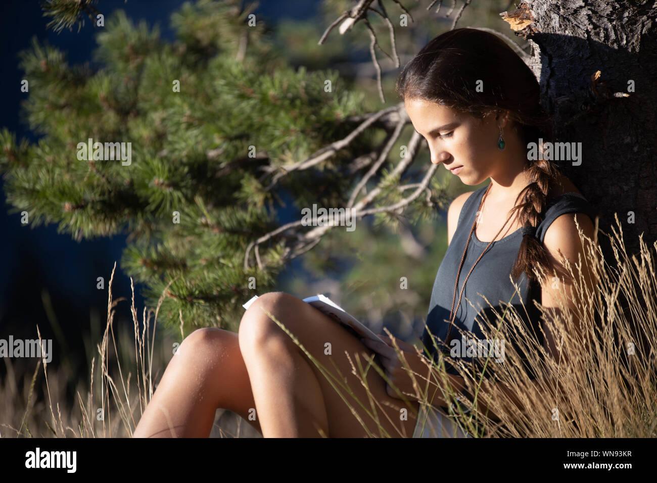Chica adolescente leyendo un libro el exterior Stock Photo