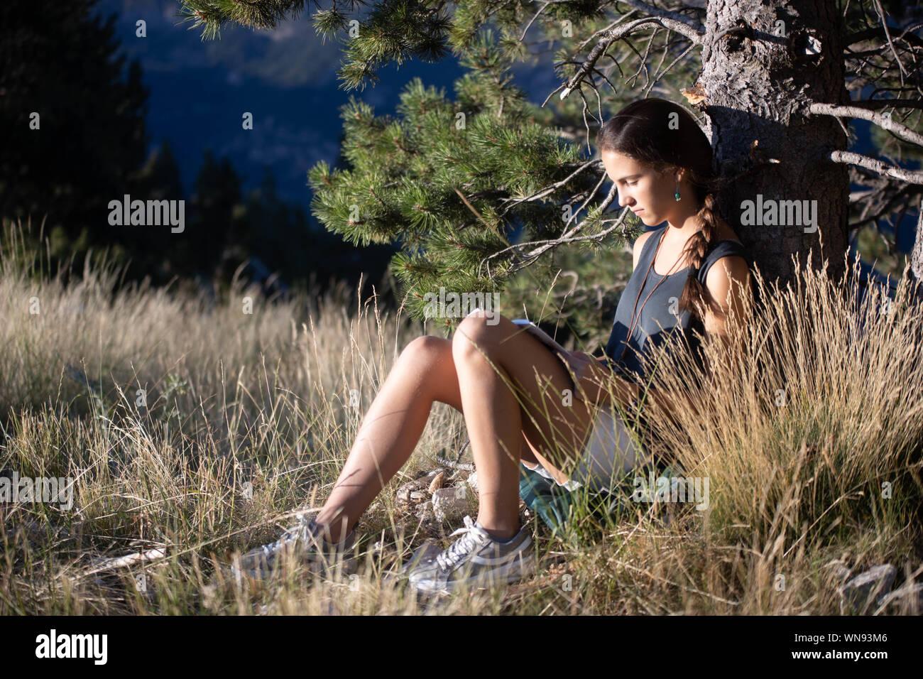 Chica adolescente leyendo un libro el exterior junto a un árbol Stock Photo