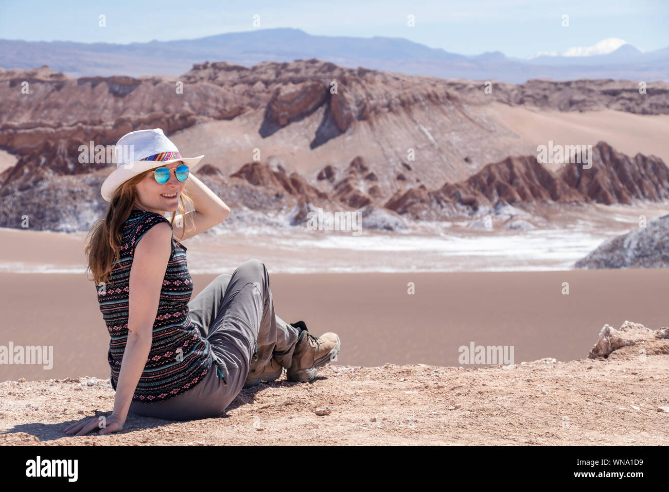 Young blond caucasian woman alone sitting and admiring untouched nature of Moon Valley in Atacama desert, Chile. Outstanding landscape background with Stock Photo
