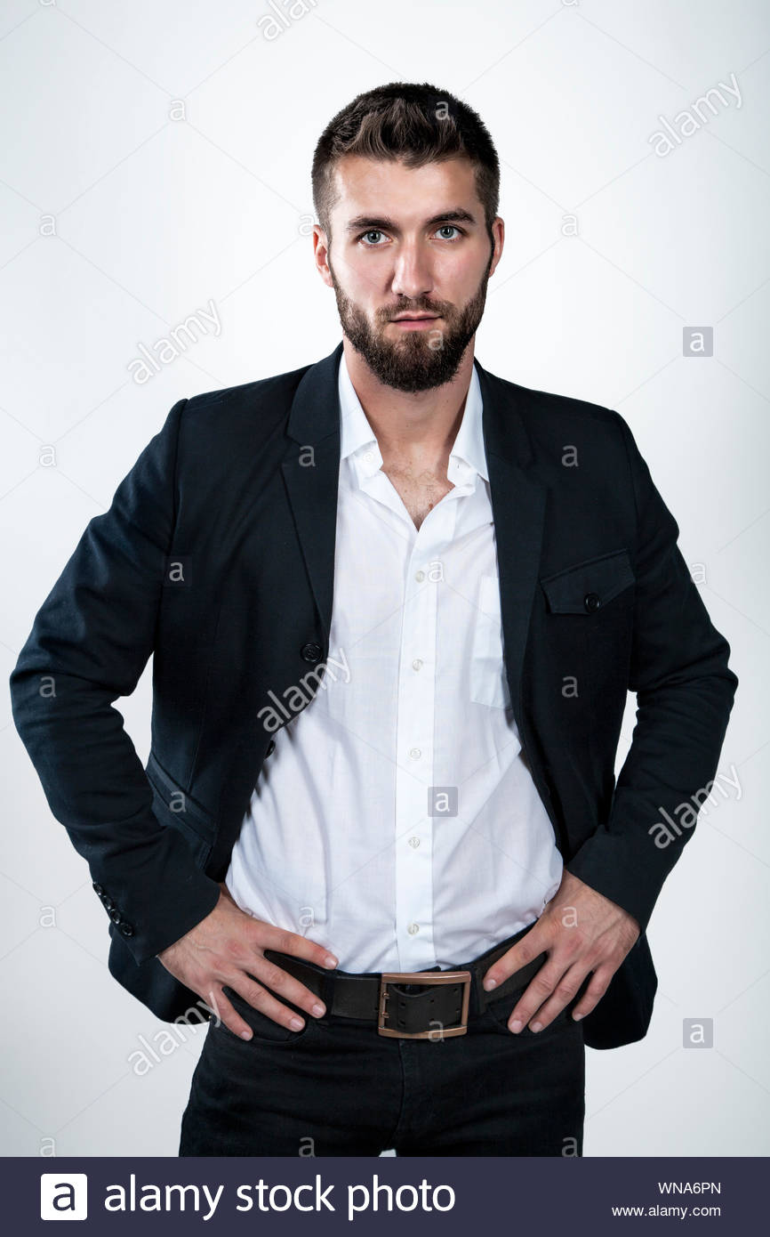 Portrait Of Confident Businessman With Hands On Hip Against White Background - Stock Photo