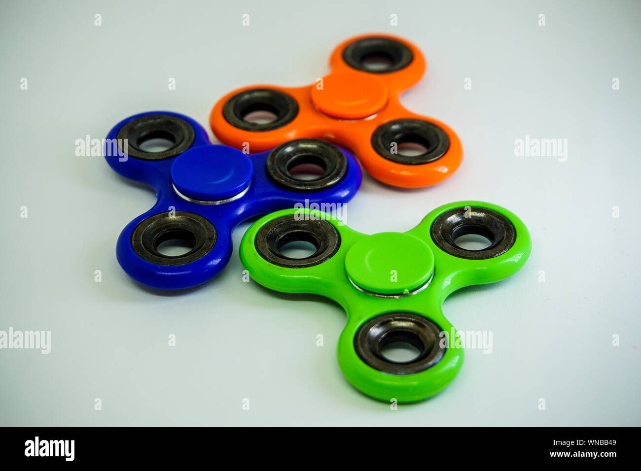 Close-up Of Colorful Fidget Spinners On White Table Stock Photo