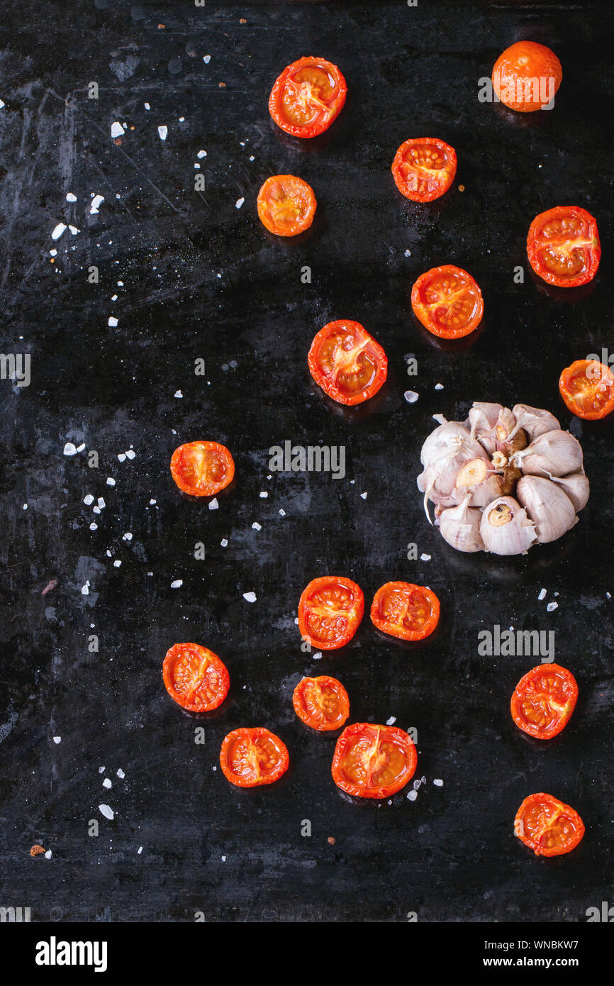 Directly Above Shot Of Garlic And Sun Dried Tomatoes With Rock Salt On Baking Sheet Stock Photo