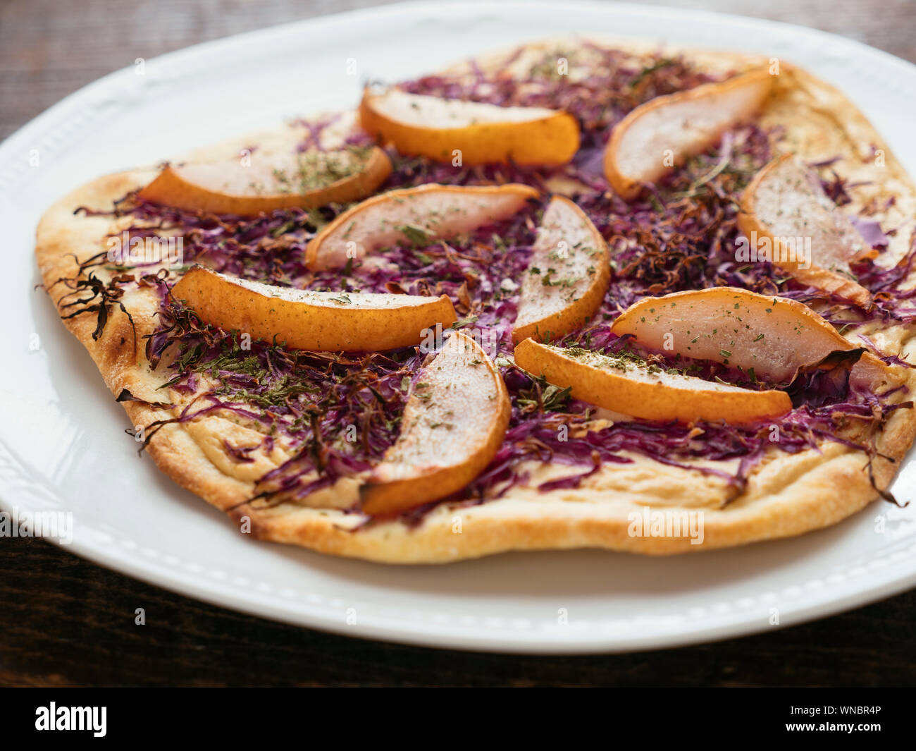 Traditional German flammkuchen (flatbread) with red cabbage and pears. Stock Photo