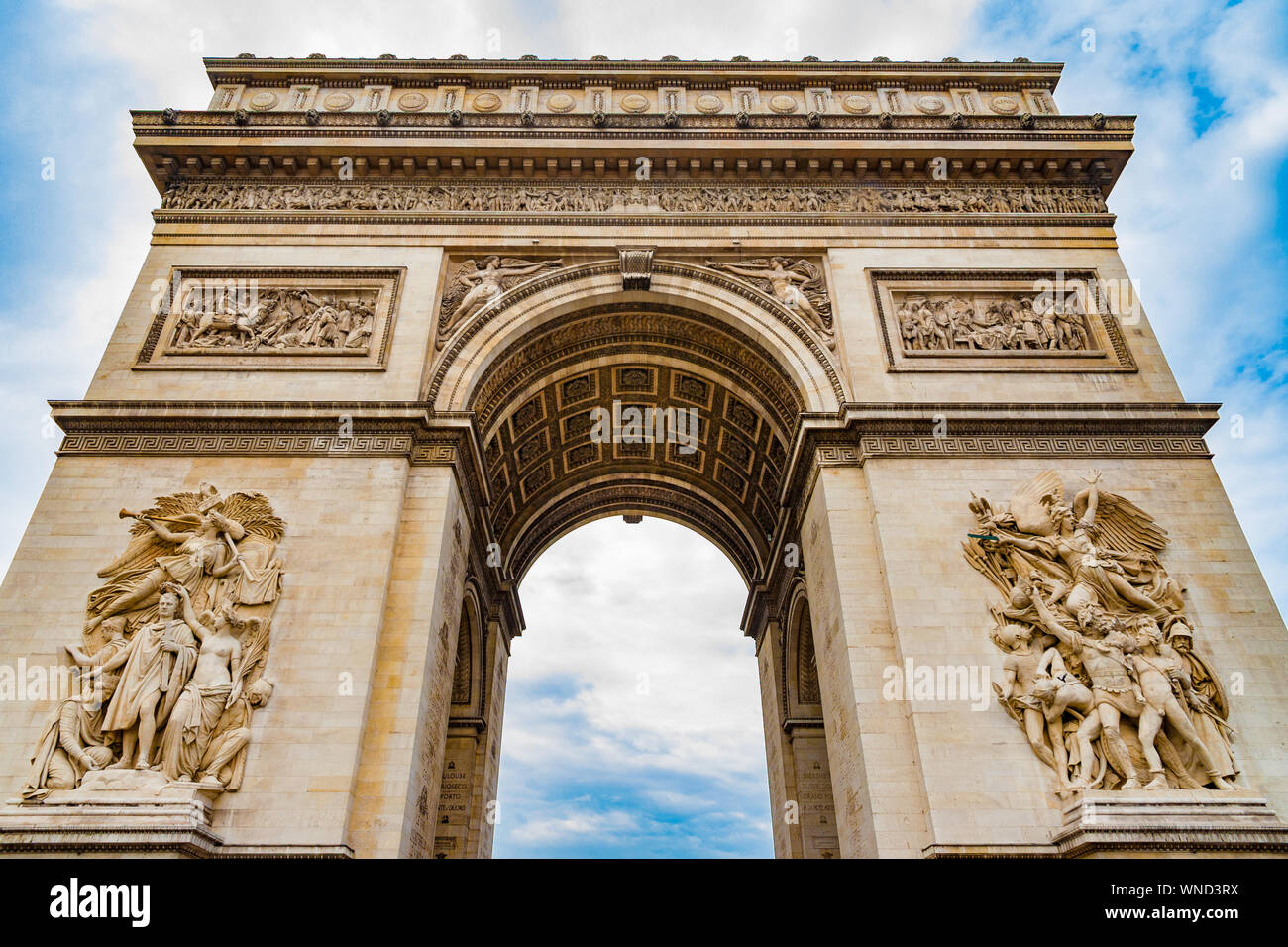 Great low angle shot of the stately Arc de Triomphe seen from the east with the two sculptures Le Départ and Le Triomphe with a dramatic blue sky. It... Stock Photo