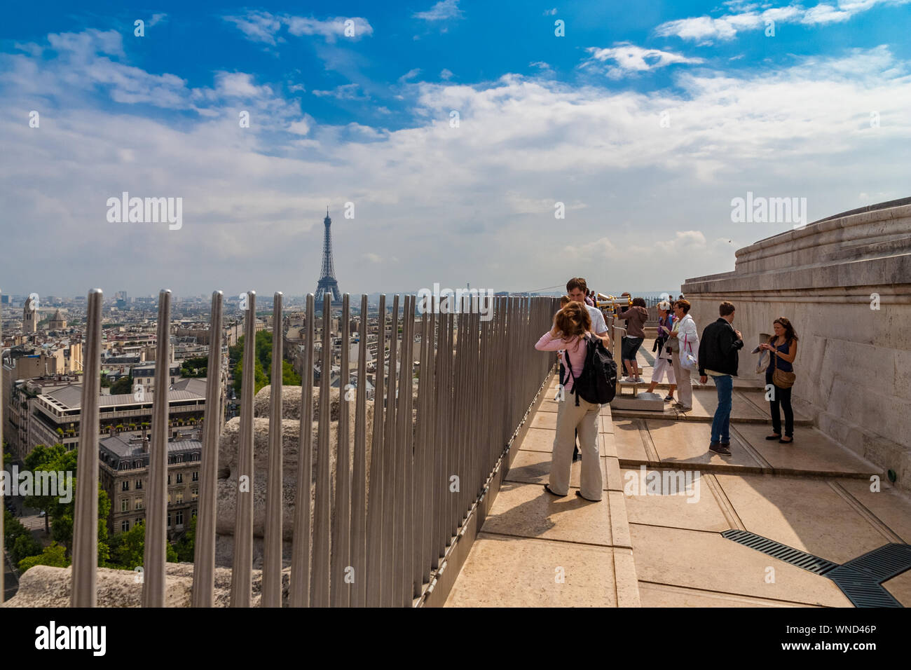 Secured by a metal fence, visitors are admiring the cityscape of Paris with the Eiffel Tower on the rooftop of the famous Arc de Triomphe on a nice... Stock Photo
