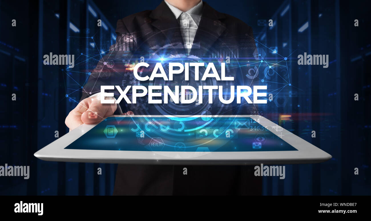 Young business person working on tablet and shows the inscription: CAPITAL EXPENDITURE, business concept Stock Photo