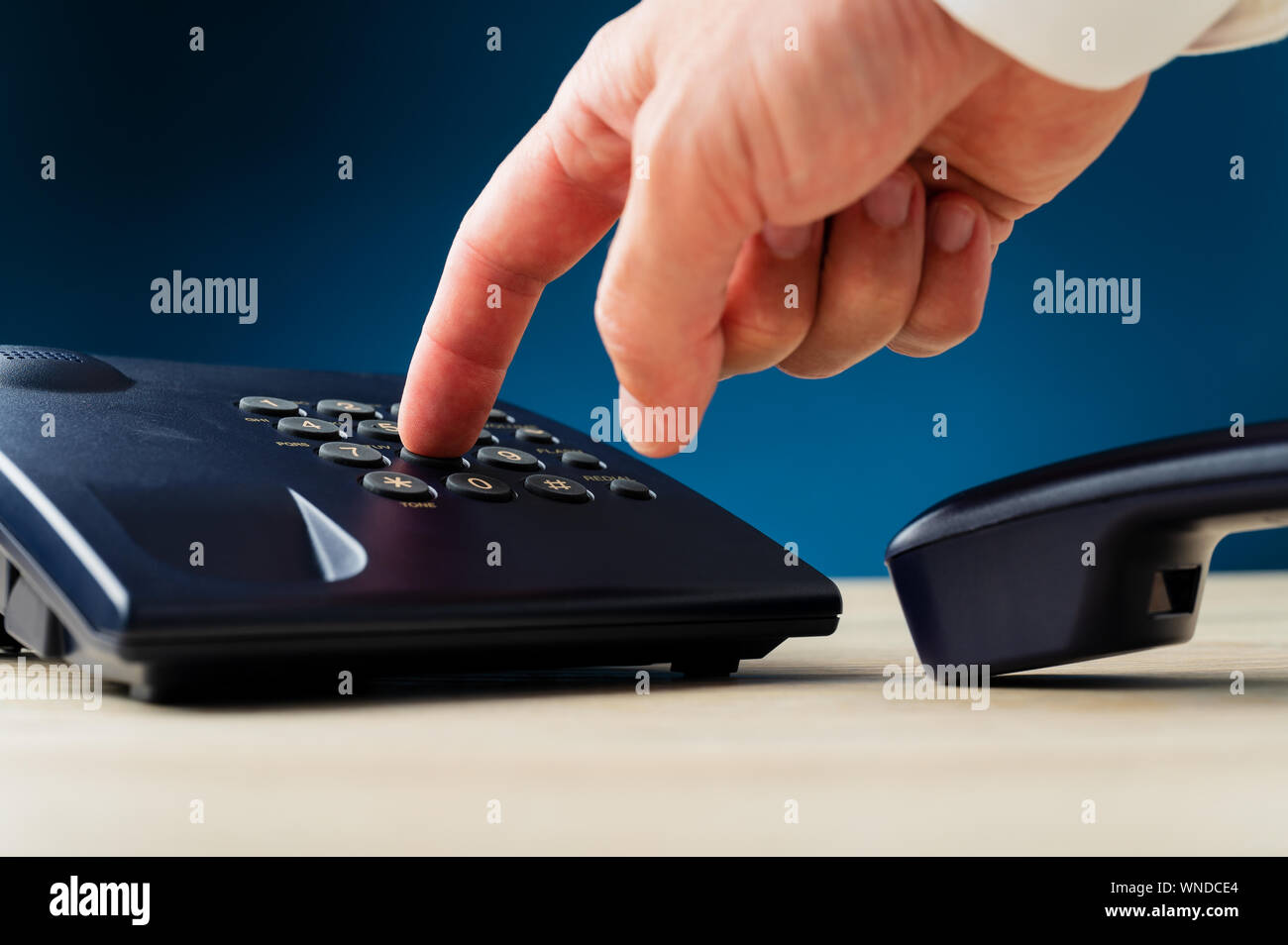 Closeup of male finger pressing a button on landline telephone keypad on a desk. Over dark blue background. Stock Photo
