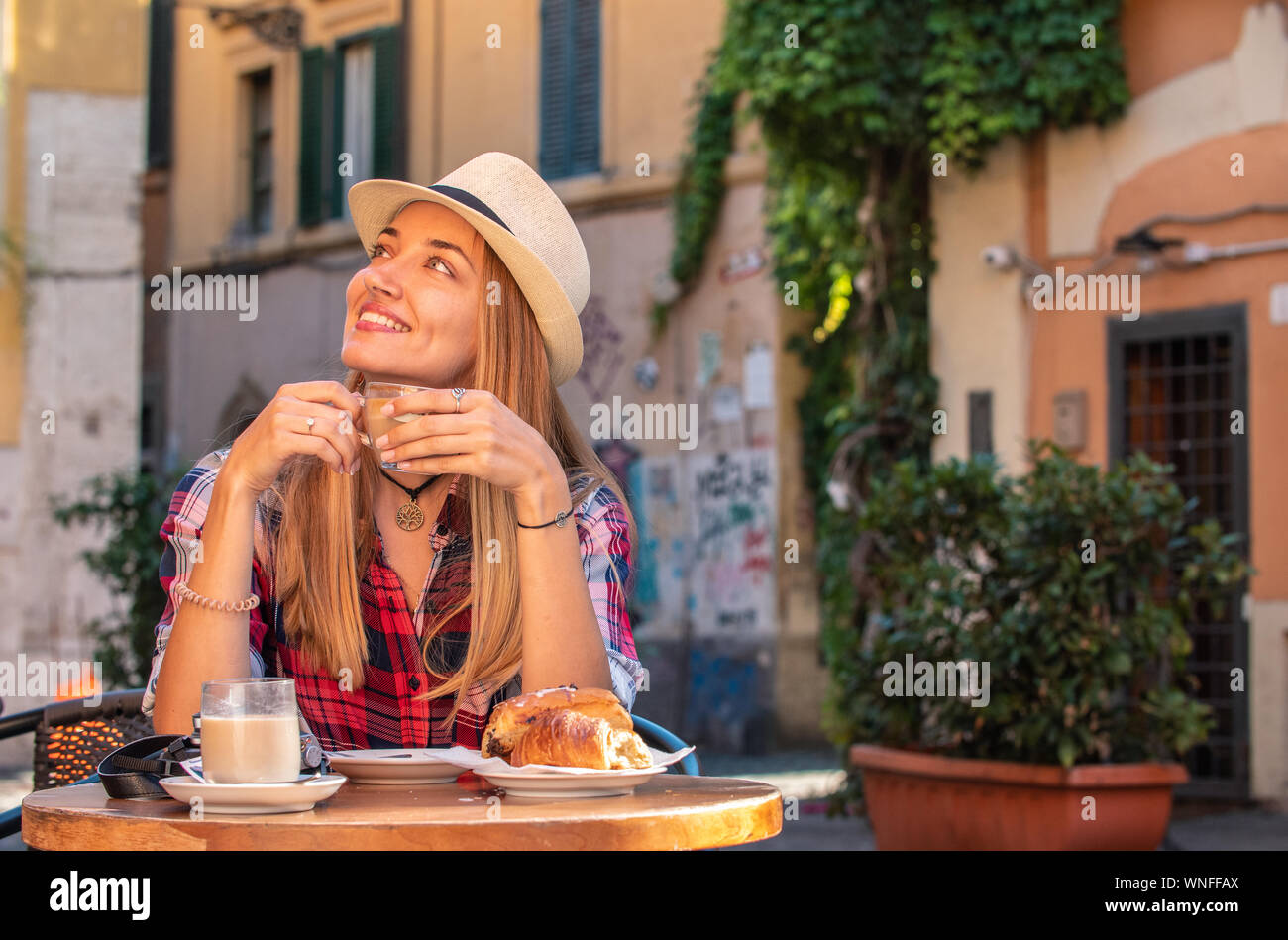 Young blonde woman with blue eyes having breakfast in typical Italian bar outside in historical neighborhood Trastevere in Rome, Italy. Cappuccino Stock Photo