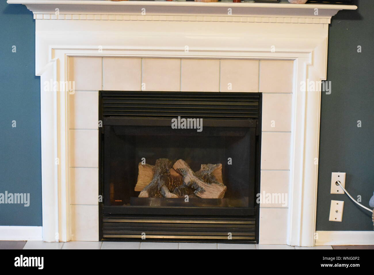 Fire Place With White Mantle And Tile Surround Stock Photo