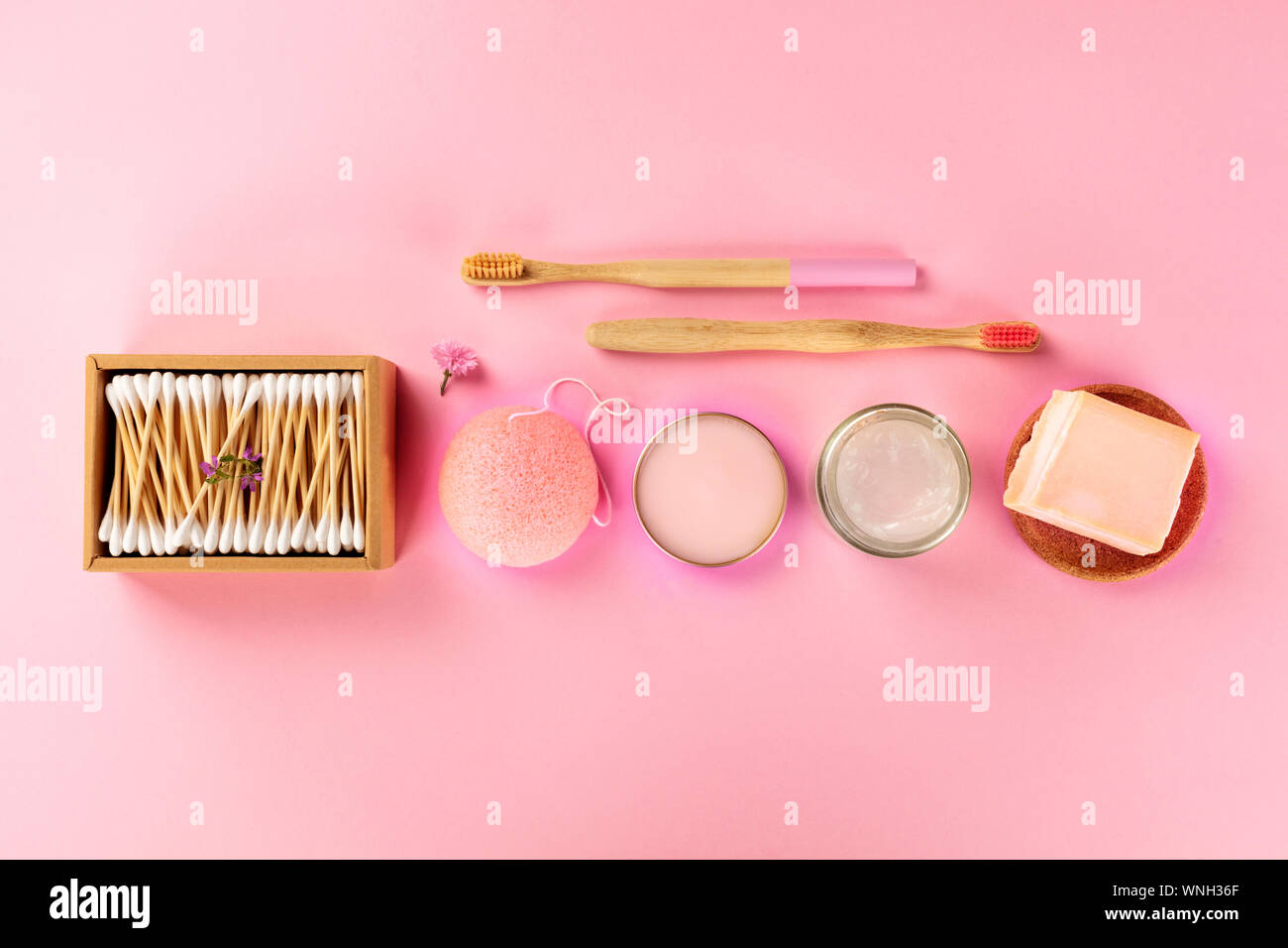 Plastic-free, zero waste cosmetics, flat lay on a pink background. Bamboo toothbrushes and cotton swabs, konjac sponge, natural organic products Stock Photo