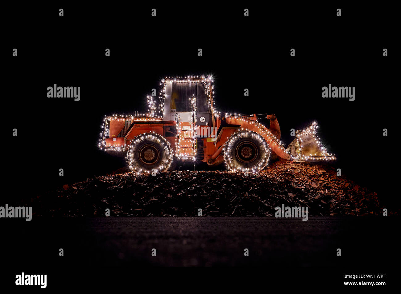 Blurred wheel loader decorated with lights at christmas Stock Photo
