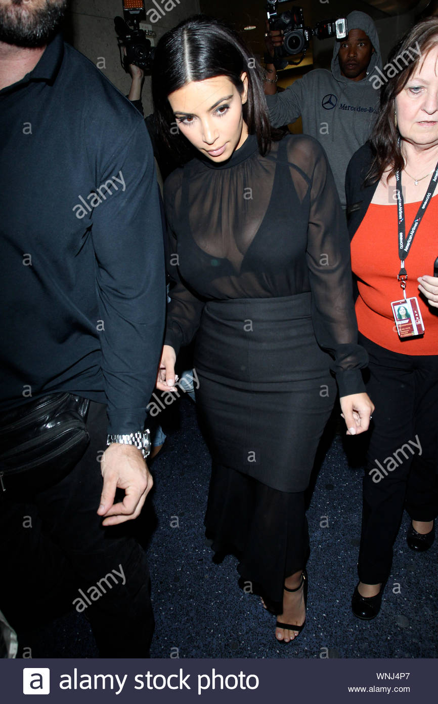 Los Angeles, CA - Kim Kardashian arrives at LAX on an incoming flight from New York and unleashes the paparazzi mayhem. Kim attended the Met Gala with her man Kanye and returned to LA alone in a see-through black blouse with a black form fitting skirt. Kim kept her head down for most of her walk to the car as her bodyguard led the way through the mass of photographers. AKM-GSI May 6, 2014 Stock Photo