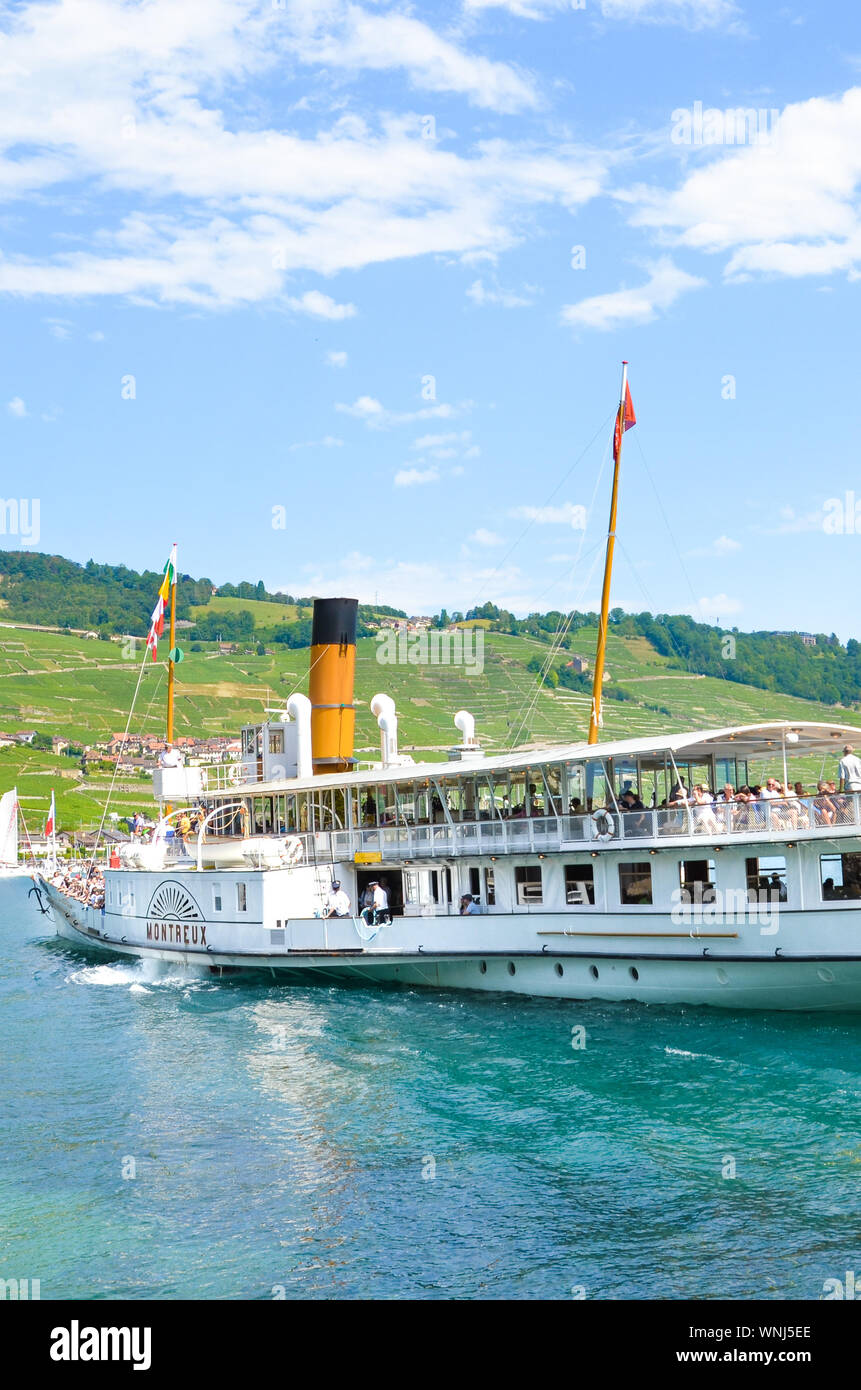 Cully, Switzerland - August 11, 2019: Sightseeing boat with tourists on Lake Geneva. Vineyards on the slopes in background. Lavaux wine region. Tourist boat, cruise. Tourism. Swiss summer. Stock Photo