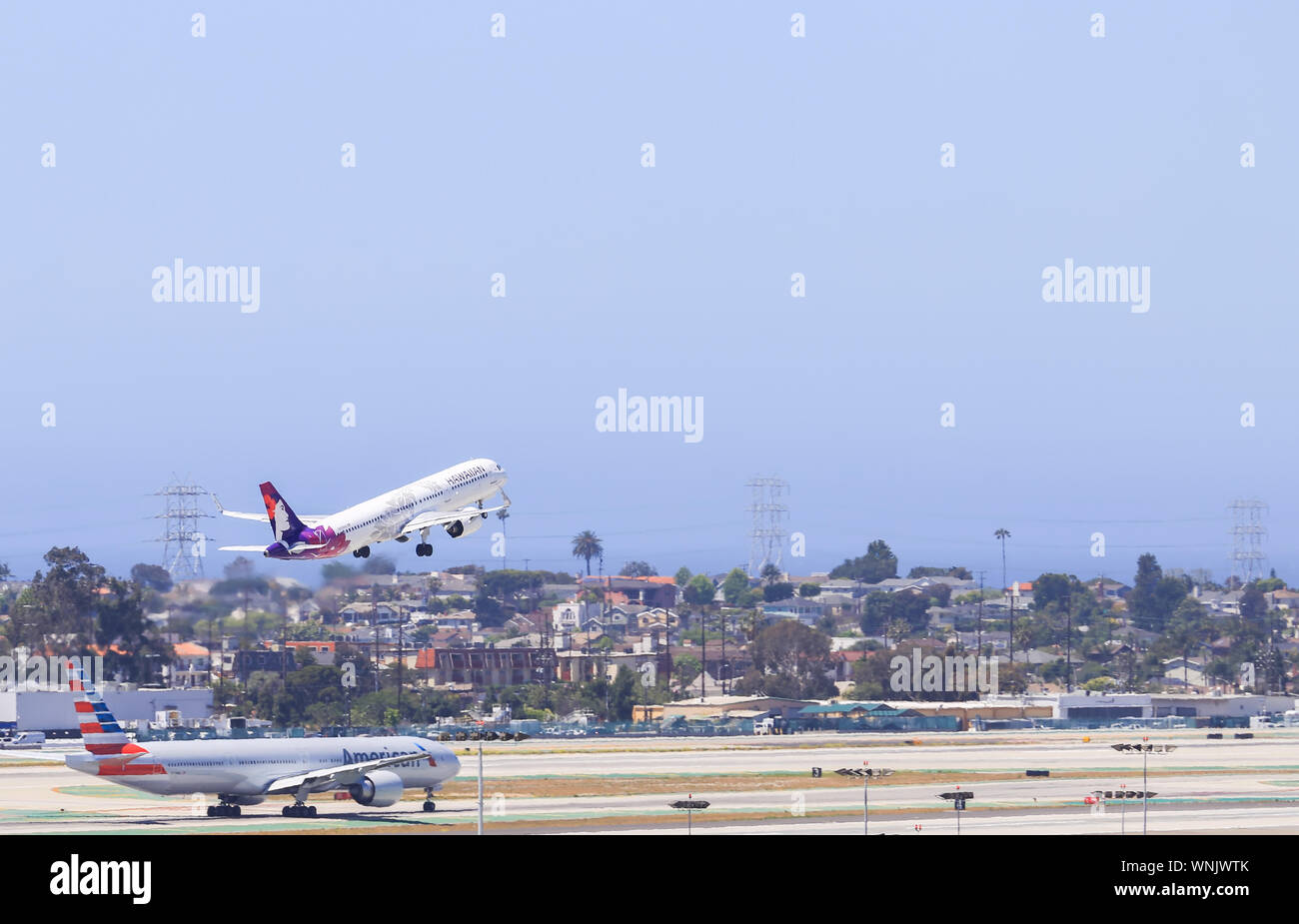 Los Angeles, California, USA - May 22, 2019: A Hawaiian Airlines plane takes off from Los Angeles International Airport (LAX). In the foreground an Am Stock Photo