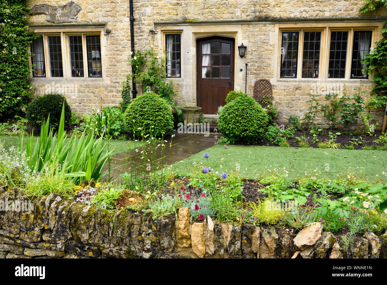 Riverside House cafe with flower garden and rock wall after a rain shower with yellow Cotswold limestone in Bourton-on-the-water England Stock Photo