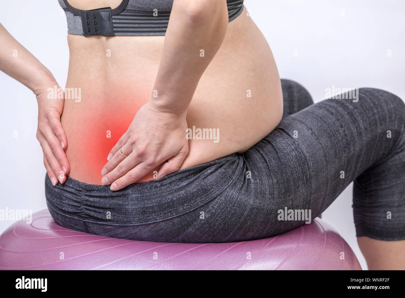 Aches and pains. Active pregnant woman exercise in fitness center at yoga room. The young expecting mother holding hands on back and sitts on fitness Stock Photo
