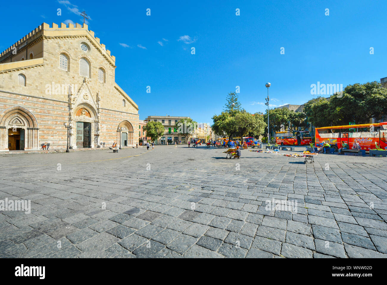 Tourists visit the Messina Cathedral and it's ornate bell tower on the Piazza Duomo in the Sicilian city of Messina, Italy. Stock Photo