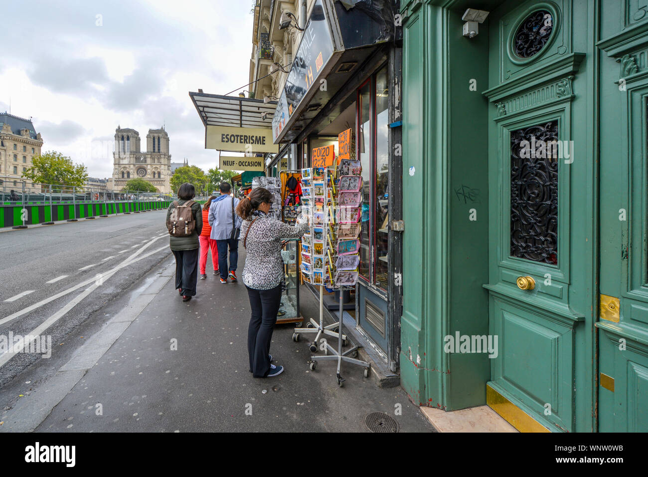 A tourist searches for postcards in Paris, France, at a sidewalk souvenir shop on the banks of the Seine River with the Notre Dame Cathedral in view Stock Photo