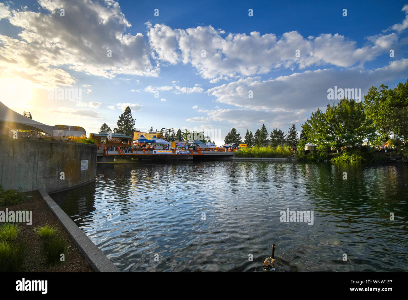 The sun begins to set at dusk over the tents, booths and vendors at the annual Pig out in the Park at Riverfront Park in Spokane, Washington, USA Stock Photo