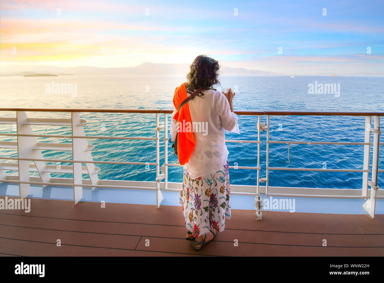 A woman sips a drink on the deck of a cruise ship as the sun sets and the ship passes islands on the Aegean Sea Stock Photo