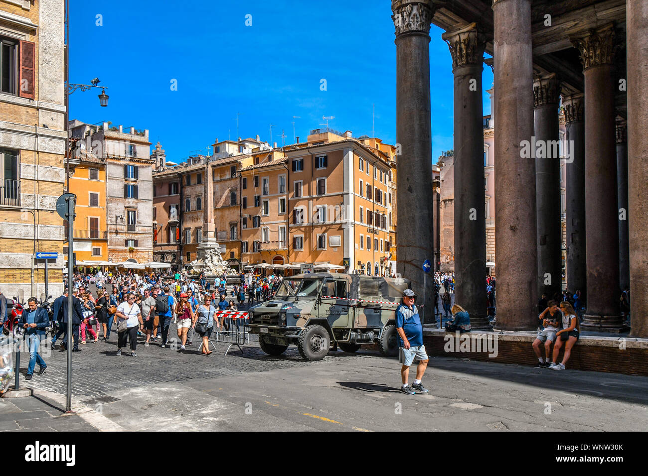 Tourists sightsee at the ancient Pantheon as tourists crowd the Piazza della Rotonda and the Fontana dei Pantheon and obelisk as soldiers secure area Stock Photo