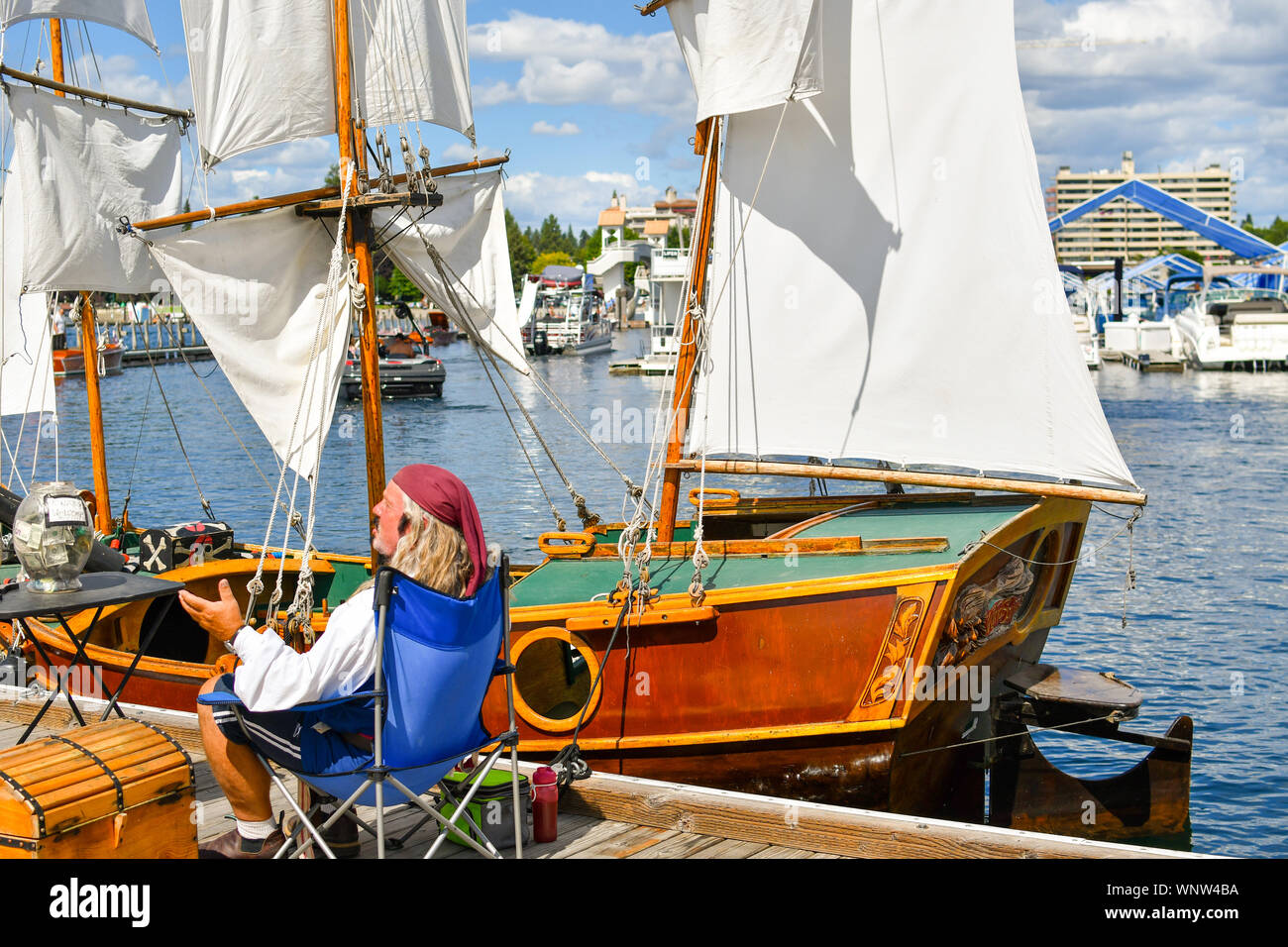 A boat owner dressed as a pirate near his miniature replica ship based on Columbus ships docked at the marina for the wooden boat show. Stock Photo