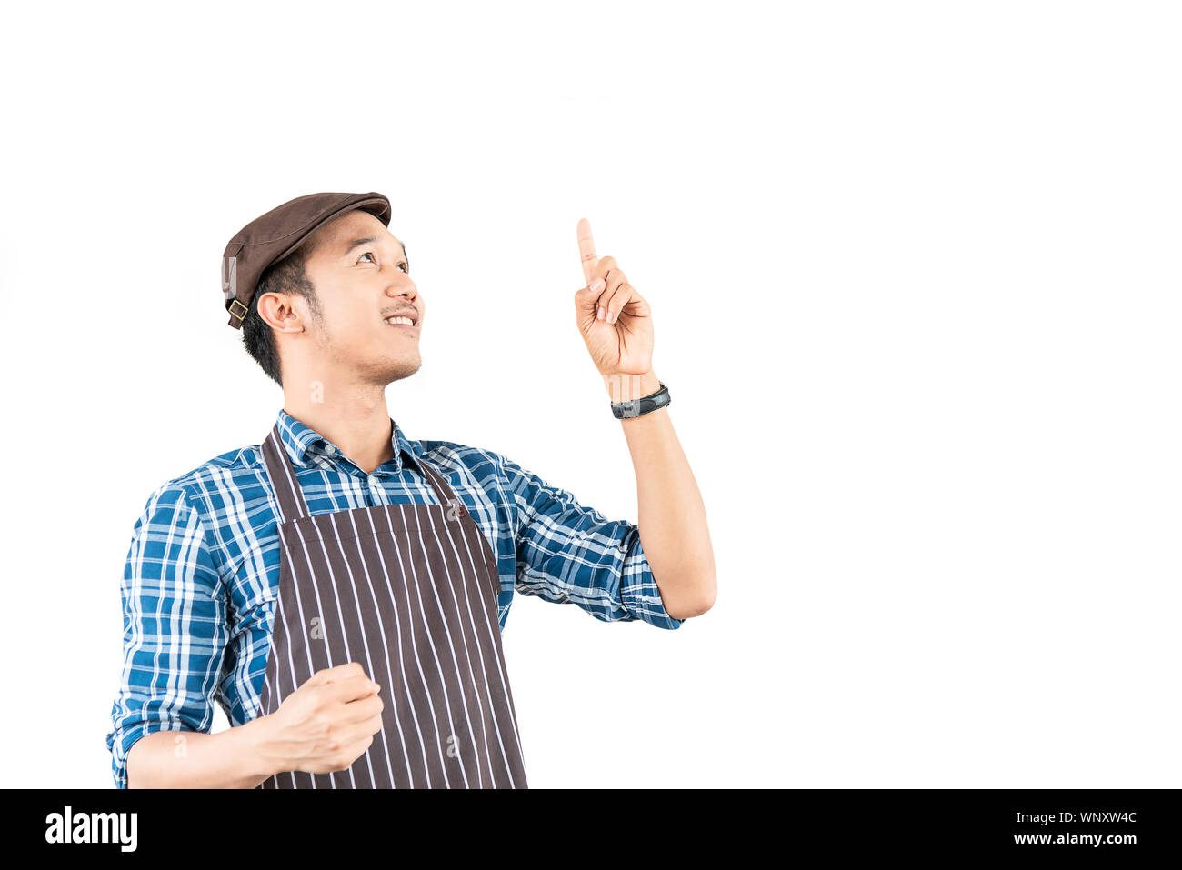 The young asian man who is wearing an apron confidently smile and point to something above him isolated on white background. Portrait man with copy sp Stock Photo