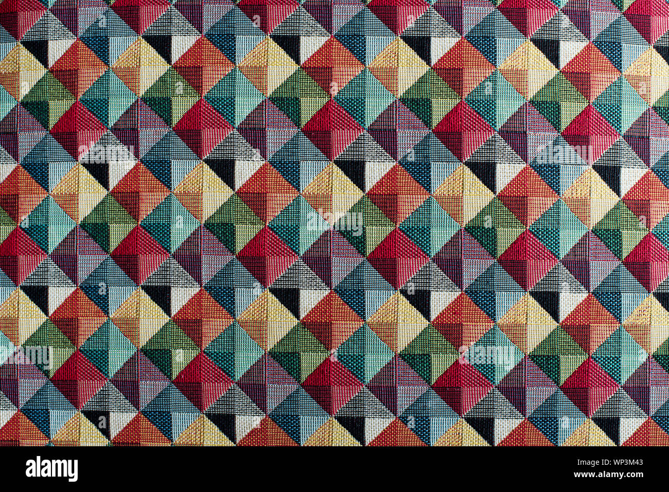 Geometric multicolored textile background pattern in a full frame view of diamond or square shapes with color shading Stock Photo