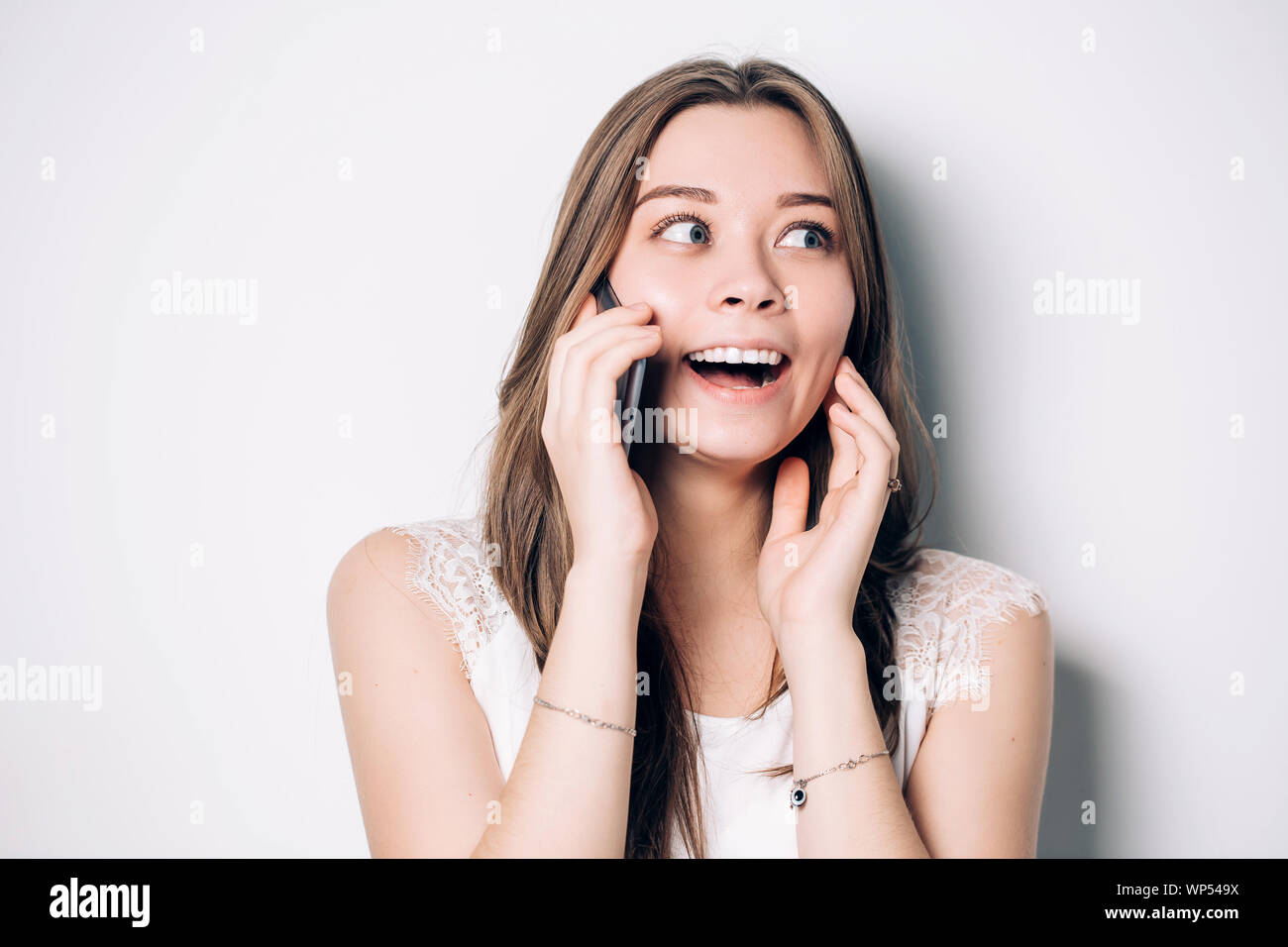 Happy woman phone talking. Face with toothy smile, isolated over white Stock Photo