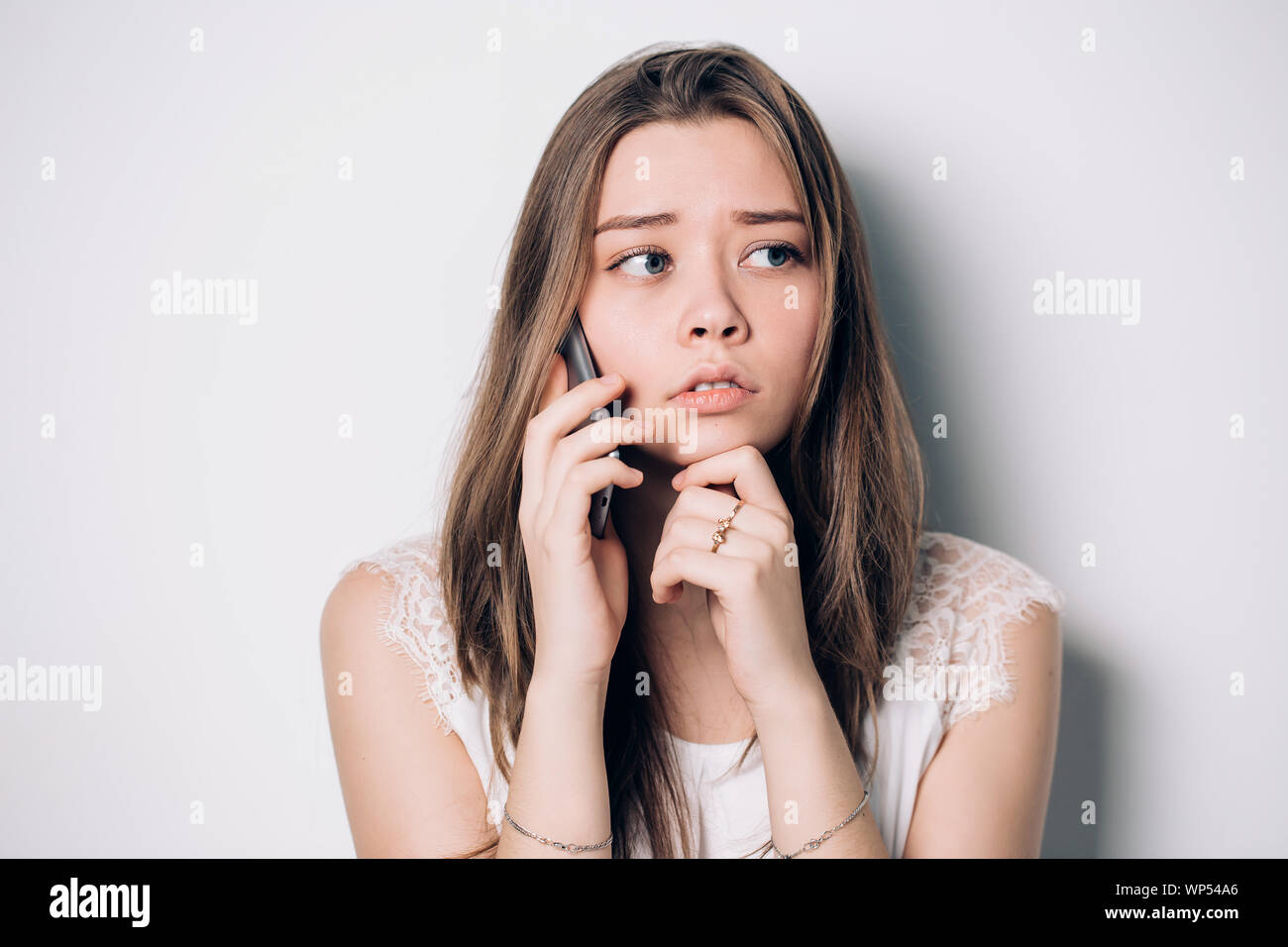 Frustrated annoyed sad woman with mobile phone. Young upset woman talking on phone in office. Unhappy, sad girl, emotions, expressive facial features Stock Photo