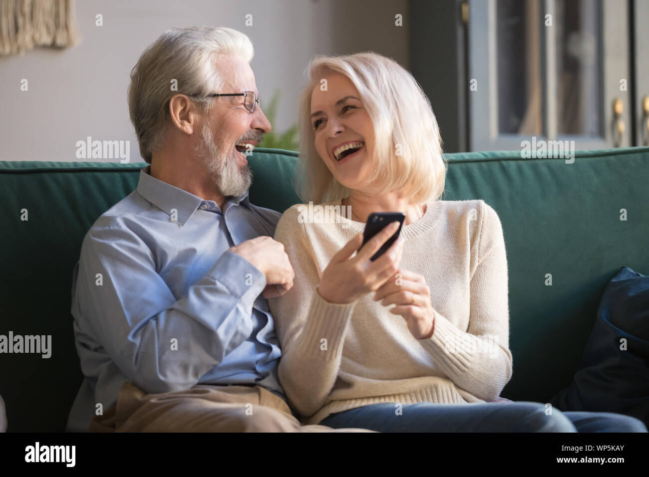 Happy retirees family laughing using smartphone at home. Stock Photo