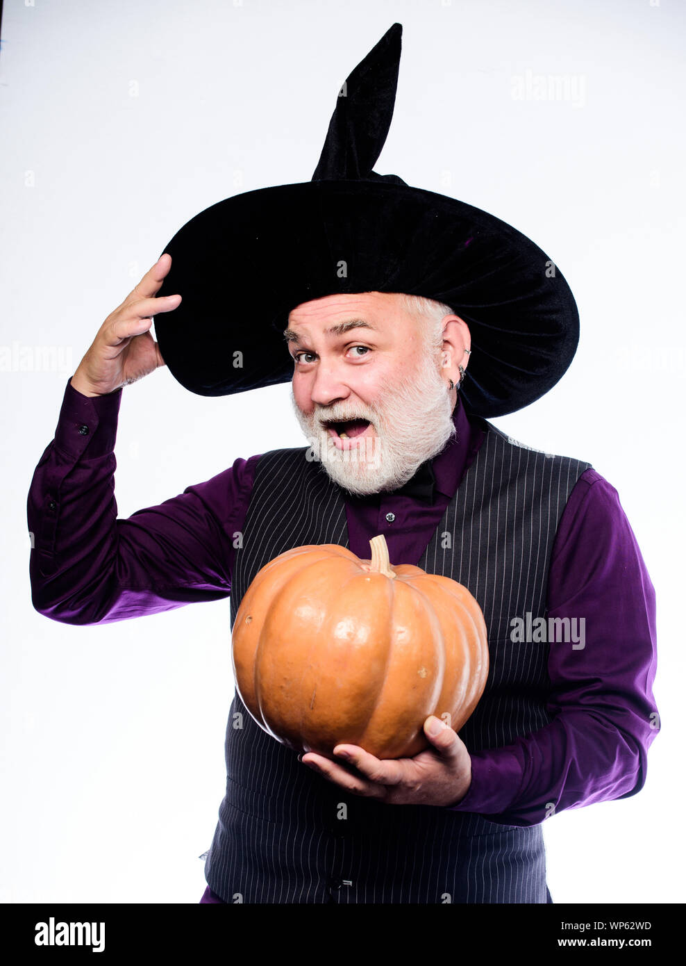 Fantastically good fun. Stargazer in holiday costume. Traditional food. bearded man ready for halloween party. evil wizard hold orange pumpkin. happy halloween. mature man magician in witch hat. Stock Photo