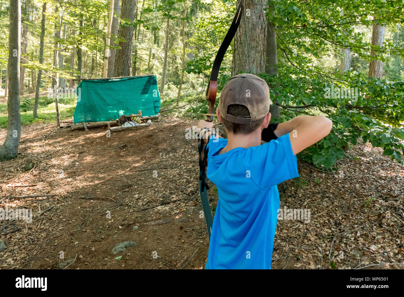 boy with cap and blue shirt shooting bow Stock Photo
