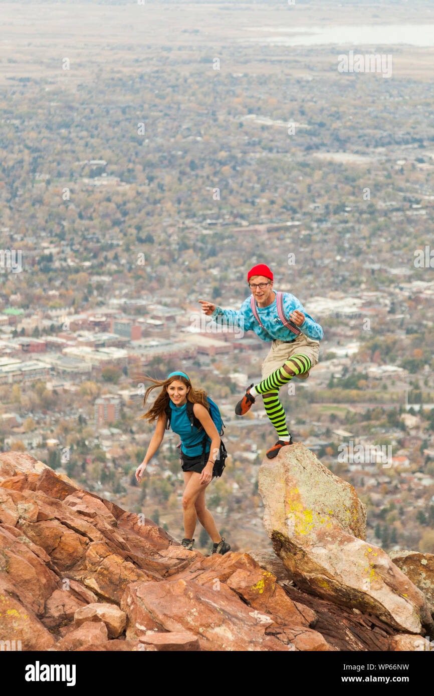A couple of climbers in silly costumes scramble over the false summit on First Flatiron's North Arete (5.4) above Boulder, Colorado. Stock Photo