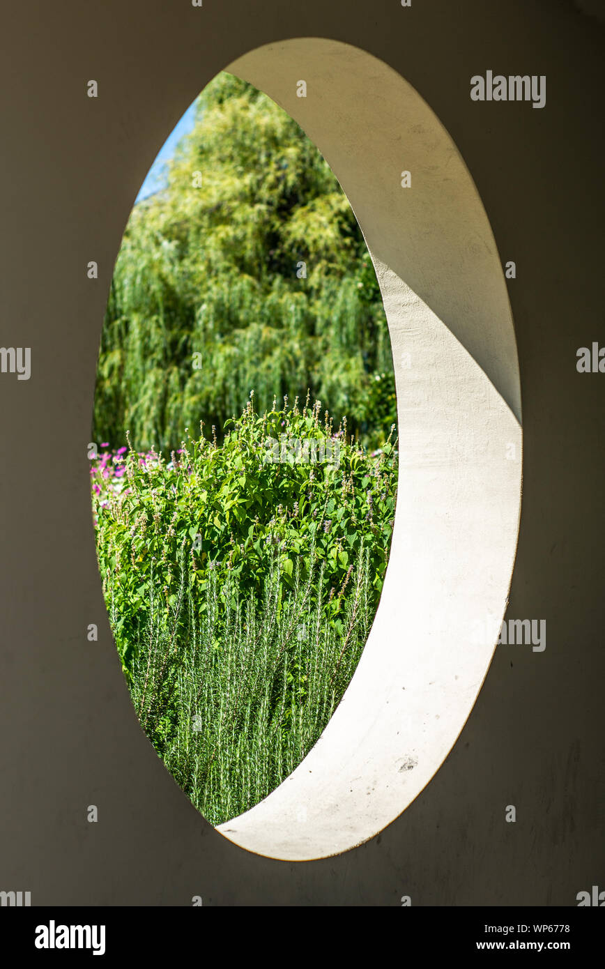 A view on a colorful garden in summer through a round hole in a concrete wall Stock Photo