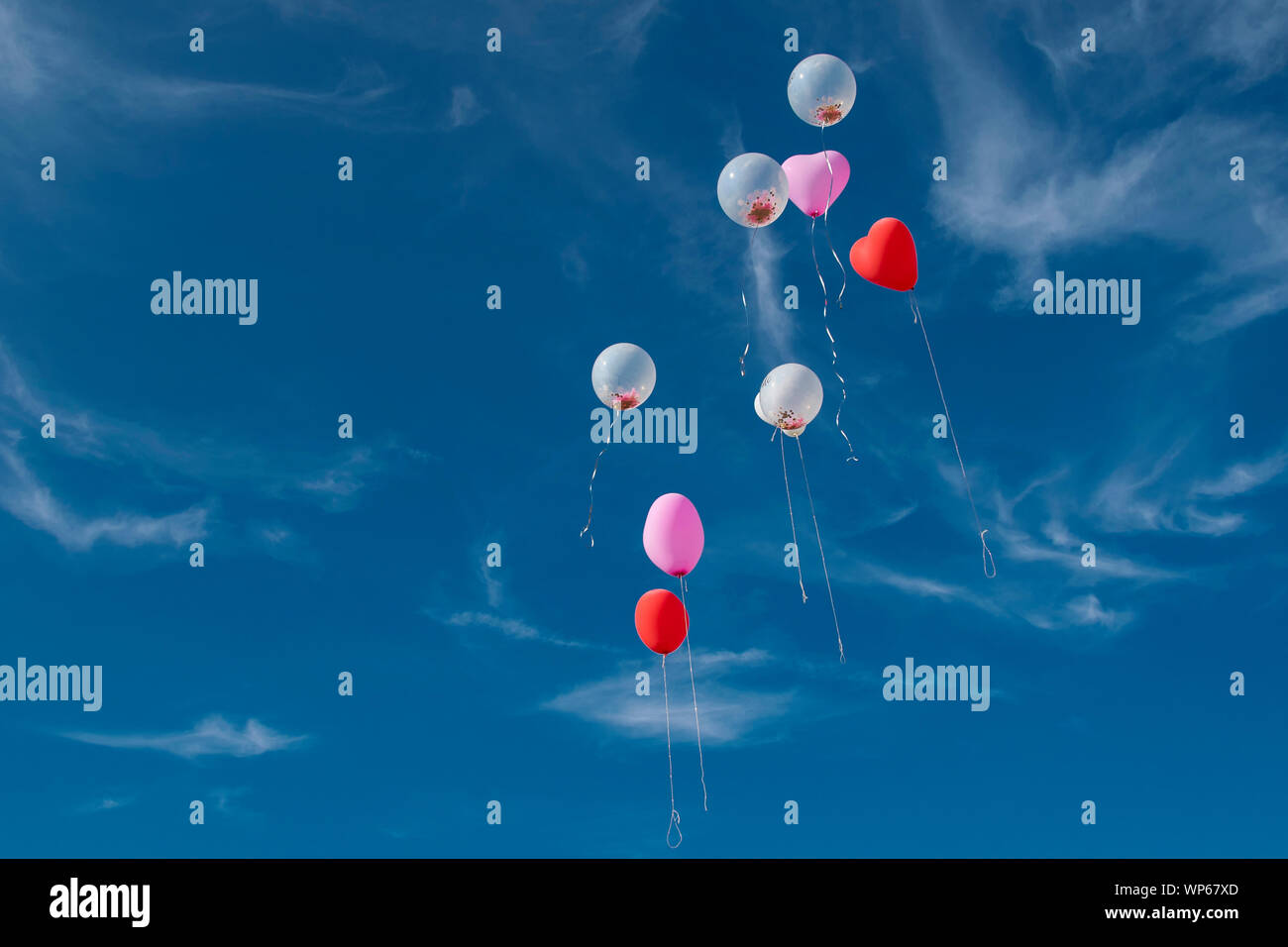 red heart shaped balloon in front of blue sky with clouds Stock Photo