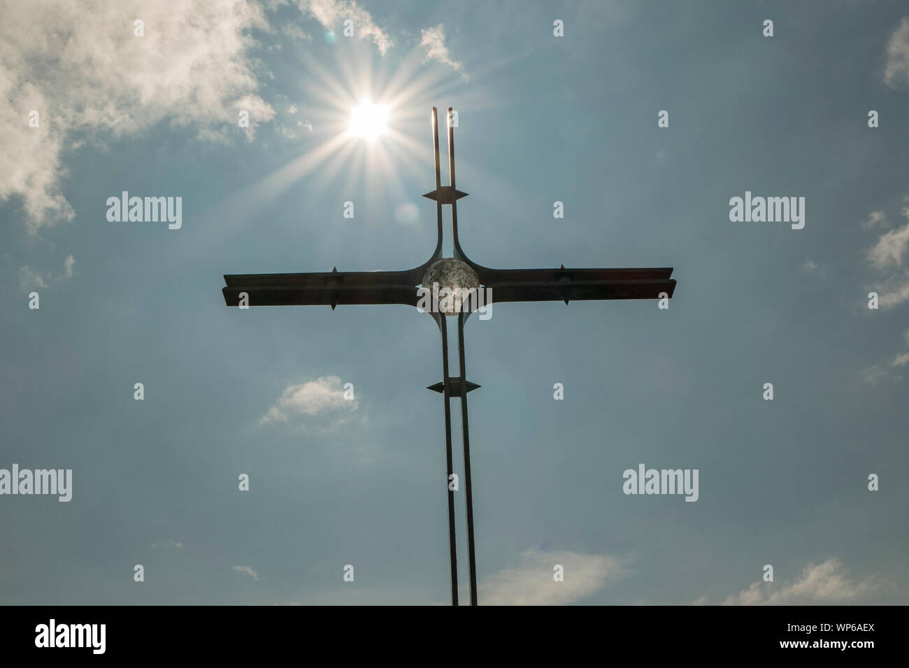Summit cross with sun in front of blue sky Stock Photo