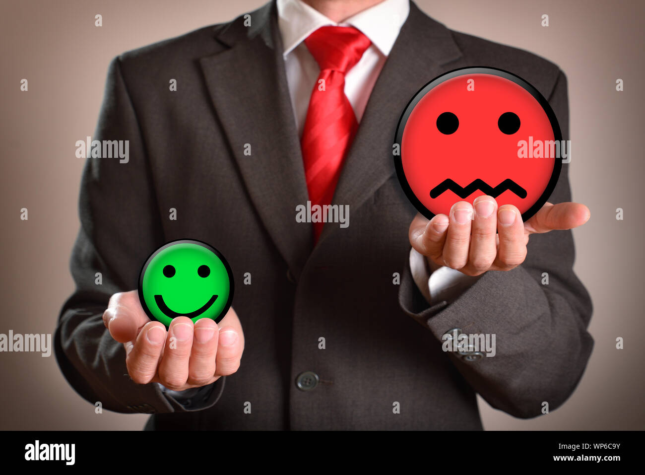 Businessman with emoticons in his hands representing failure. Horizontal composition. Front view. Stock Photo
