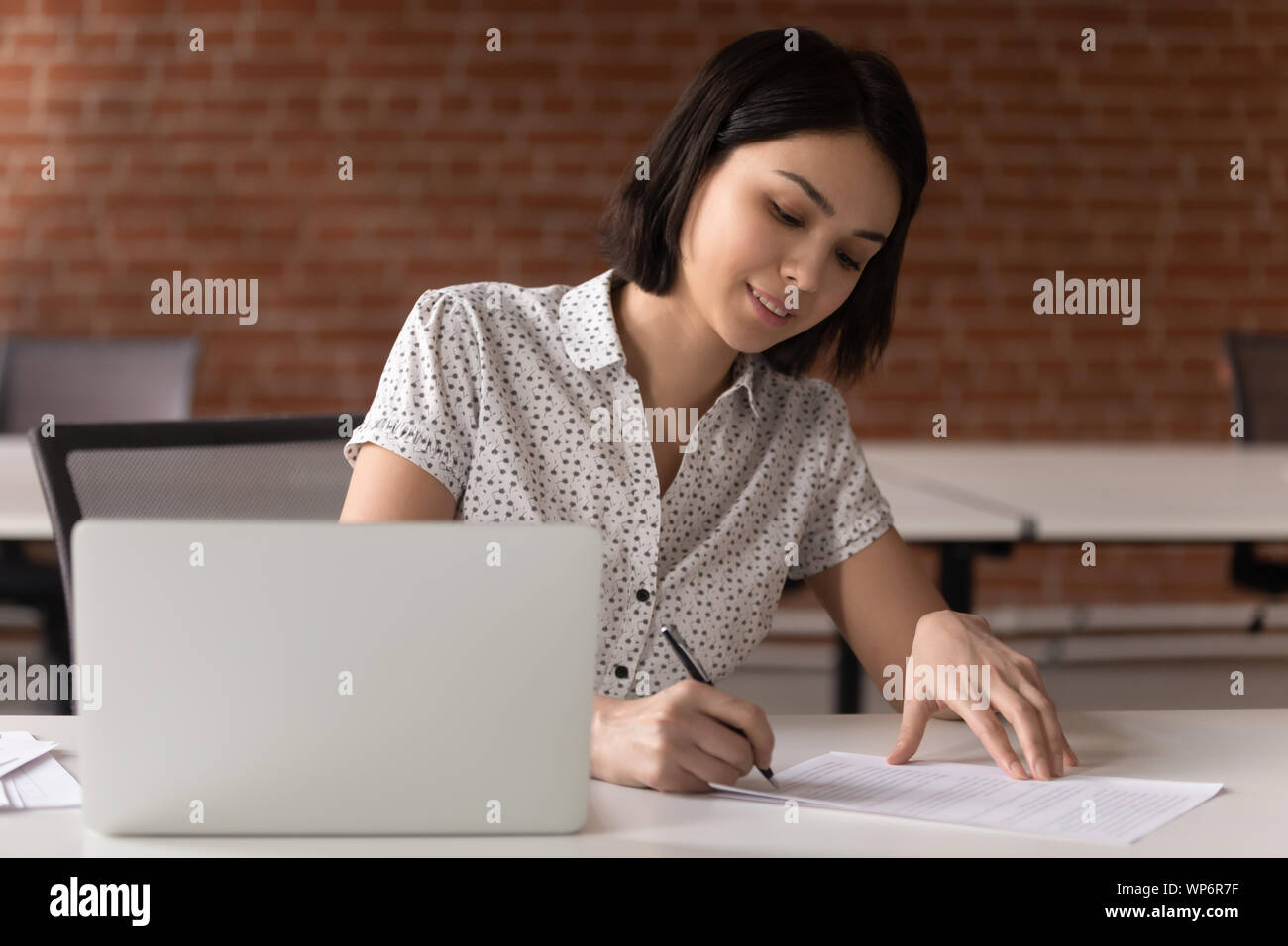 Smiling asian female executive manager signing business contract. Stock Photo