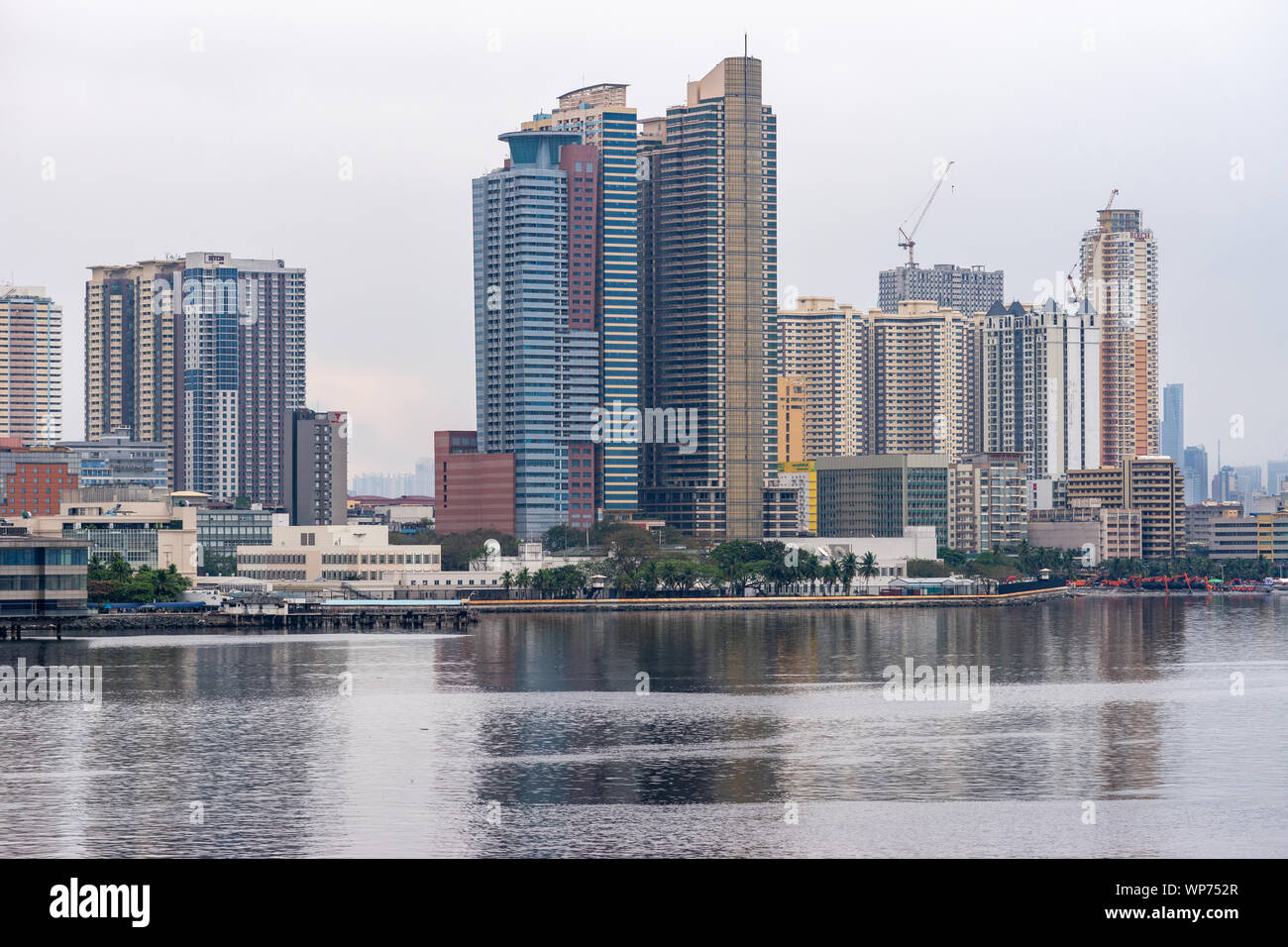 Manila, Philippines - March 5, 2019: South Harbor area early morning. Skyline with tall buildings, some under construction form horizon band between s Stock Photo