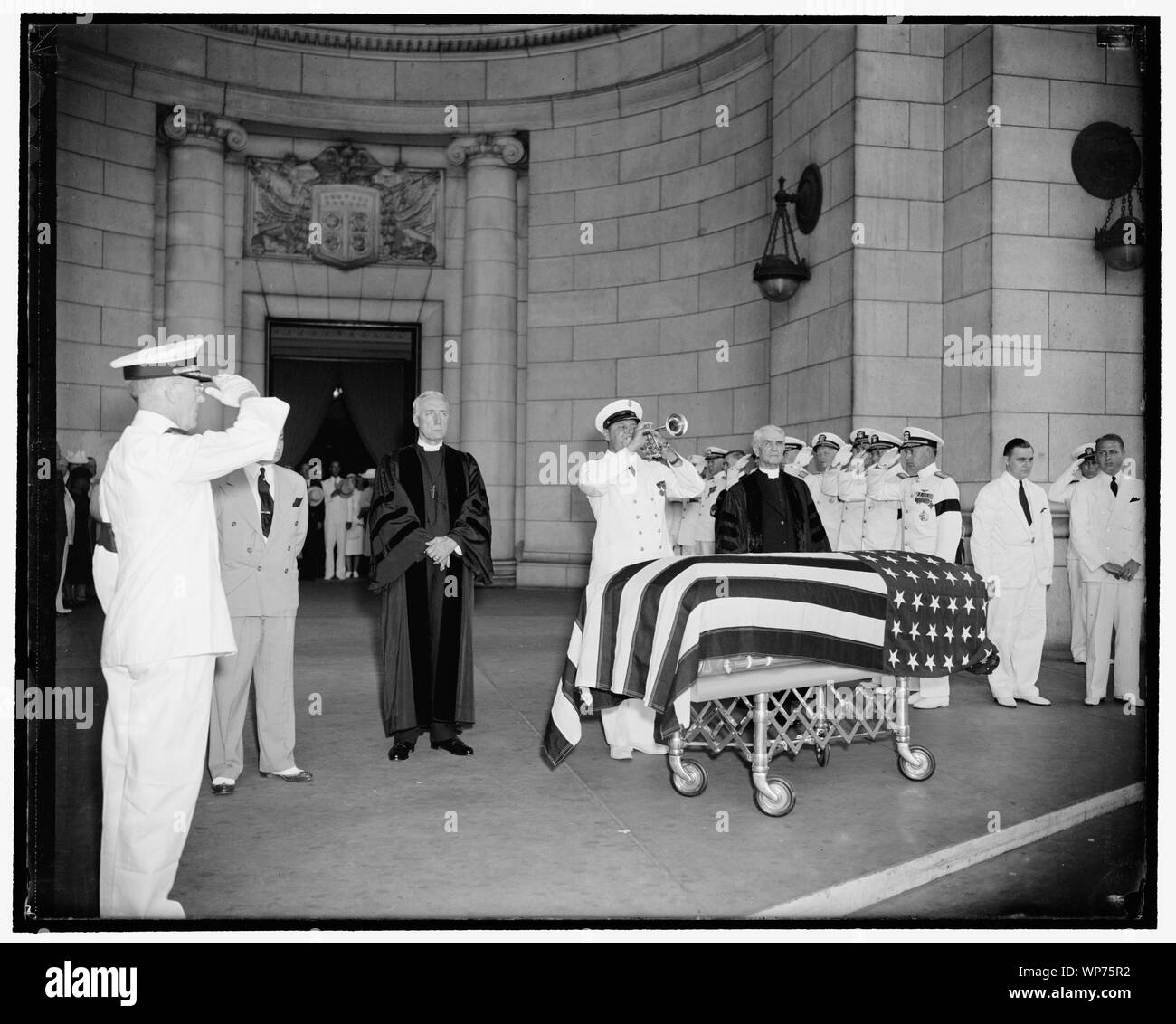 Last honors paid Navy Secretary at Union Station as bugler blows taps. Washington, D.C., July 10. While Senate Chaplain, the Rev. Ze Barney Phillips, stood on the bugler's right and the Rev. James Shera Montgomery, Chaplain of the House stood on the left, a navy bugler blew taps over the casket of Navy Secretary Swanson when the body arrived on a gun caisson at Union Station for entrainment to Richmond for the funeral Stock Photo