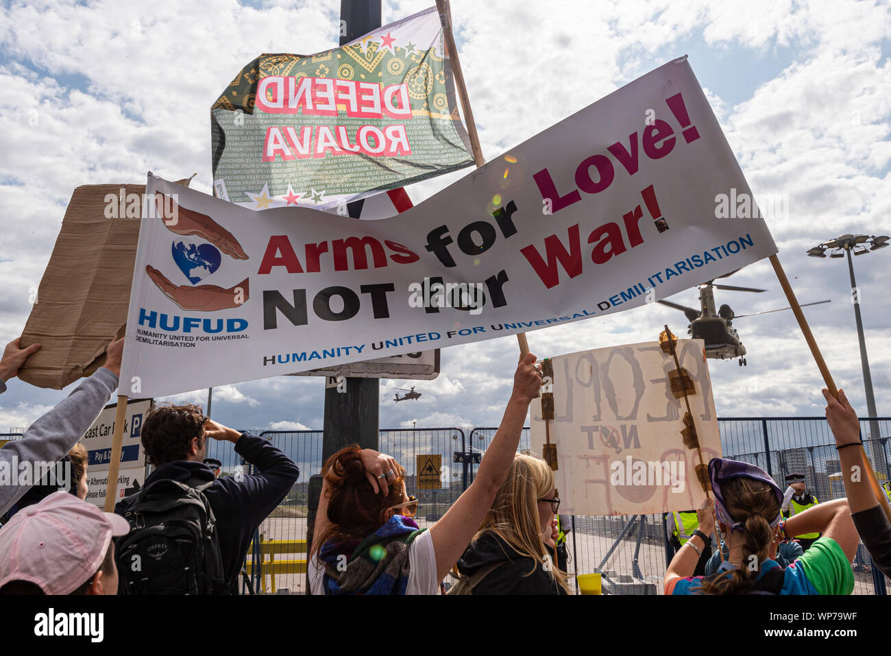 US Army Chinook helicopter landing at Defence & Security Equipment International DSEI arms fair trade show, ExCel, London, UK with protesters banner Stock Photo