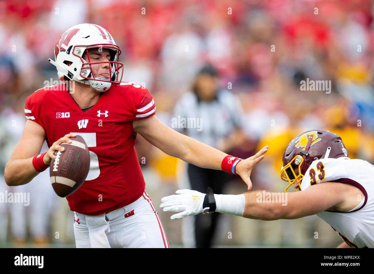 Madison, WI, USA. 7th Sep, 2019. Wisconsin Badgers quarterback Graham Mertz #5 pushes away Central Michigan Chippewas defensive lineman Keegan Cossou #93 while running to his right during the NCAA Football game between the Central Michigan Chippewas and the Wisconsin Badgers at Camp Randall Stadium in Madison, WI. John Fisher/CSM/Alamy Live News Stock Photo