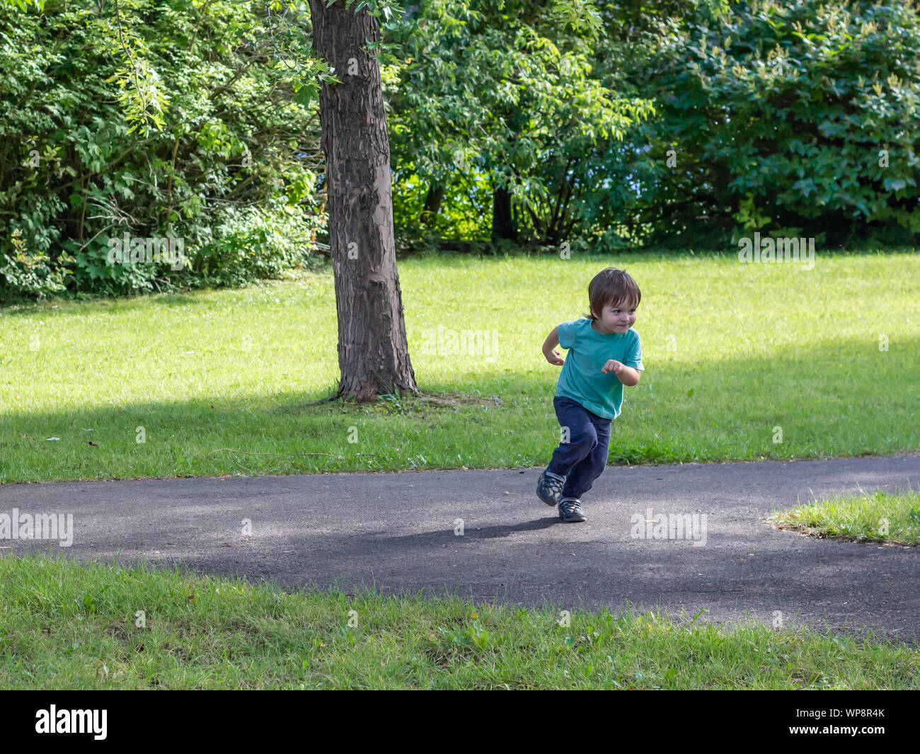A toddler of about two years of age makes an abrupt turn to take off running on a pathway in a public park. Stock Photo