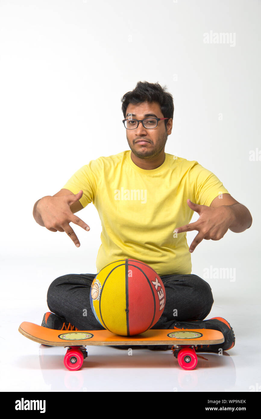 Young man sitting on floor with hip hop gesture Stock Photo