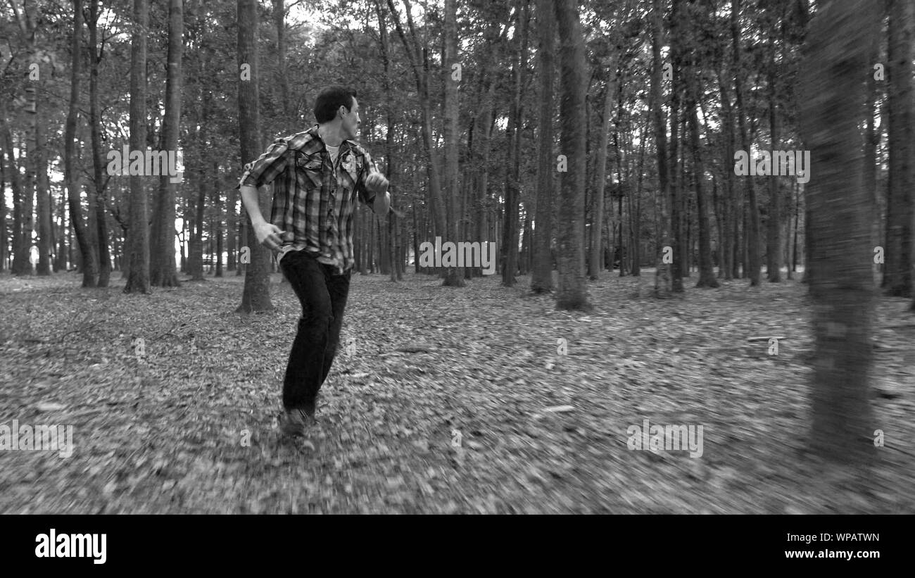 Man in fear running away from something in the forest. Stock Photo