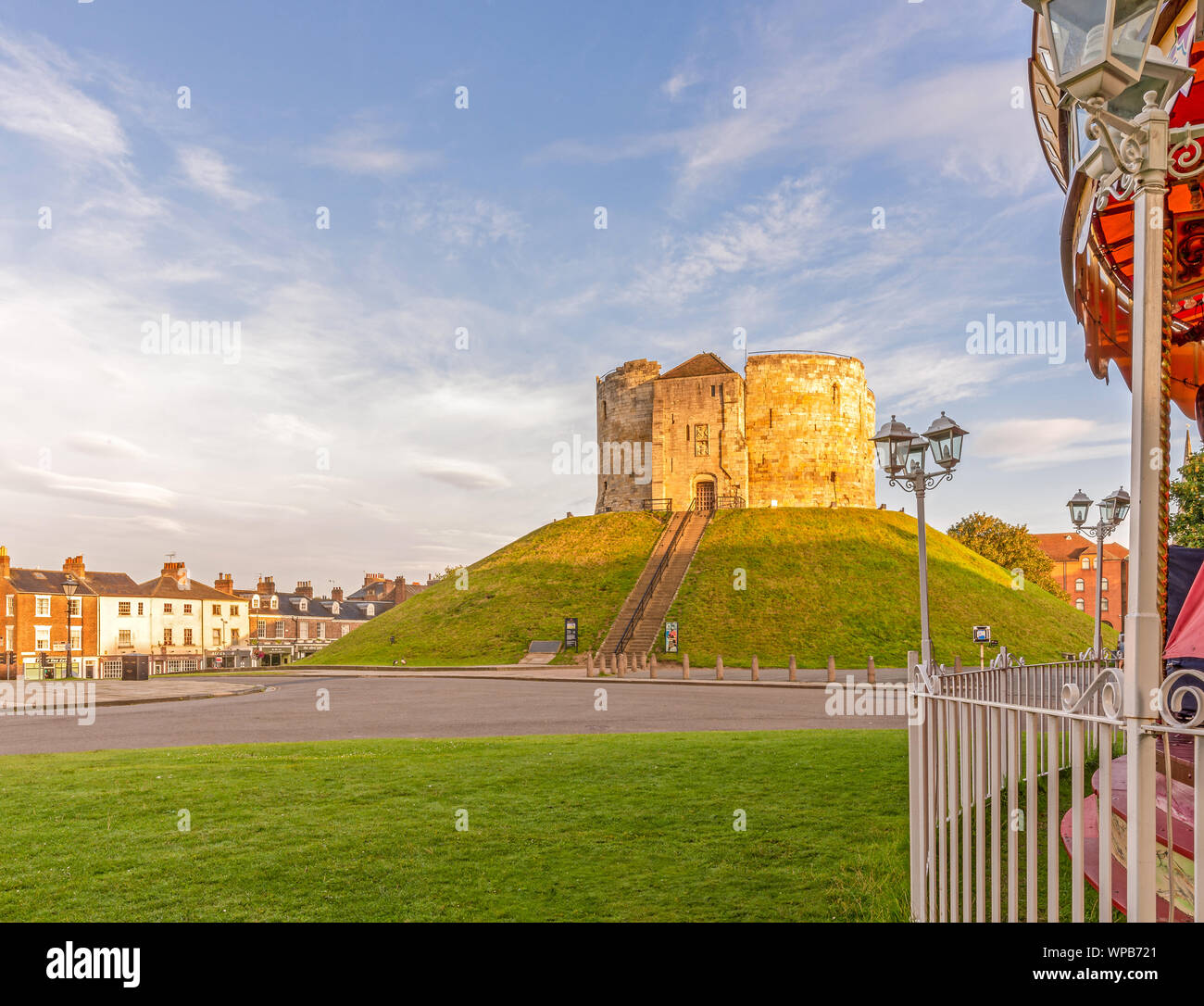 Clifford's Tower a famous York landmark caught in the golden light of dawn.  Steps lead up to the ancient tower and a carousel is in the foreground. Stock Photo